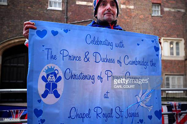 Royal supporter John Loughrey holds a banner in celebration of the christening of Prince George of Cambridge opposite St James's Palace in central...