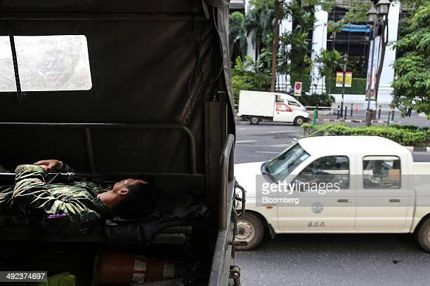 Royal Thai Army soldier holds onto his firearm while resting in the back of a military vehicle parked outside luxury hotels on Ratchadamri Road in...