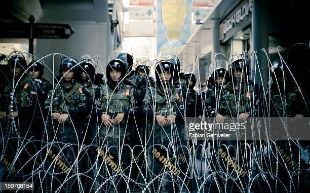 CONTENT] Royal Thai Army soldiers with anti riot gear standing behind razor wire during emergency decree April 2010 in Silom Bangkok