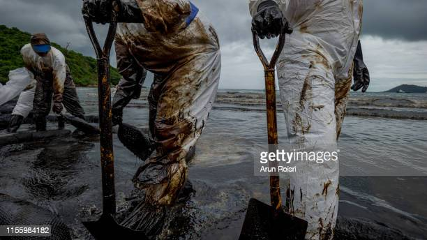 rayong, thailand - july 31, 2013: royal thai navy and local volunteers cleaning up a beach from a oil slick on ao phrao beach on samet island, rayong, thailand. an oil leak from a pipeline spilt more litres of oil into the gulf of thailand. - hydrocarbon stock pictures, royalty-free photos & images