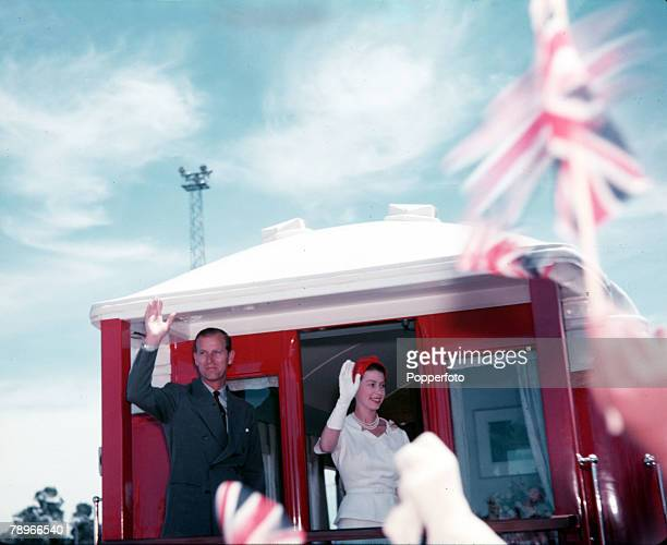 1954 Royal Tour of New Zealand Queen Elizabeth II and Prince Philip the Duke of Edinburgh wave to the crowds during a brief stop at a railway...