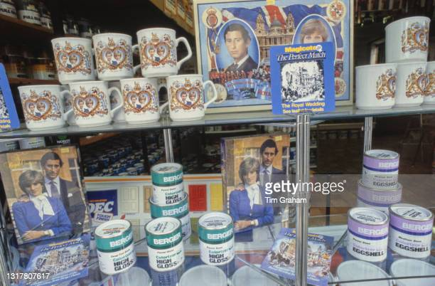 Royal Wedding memorabilia on sale alongside tins of paint on display in a shop window in the village of Tetbury, Gloucestershire, England, 14th July...