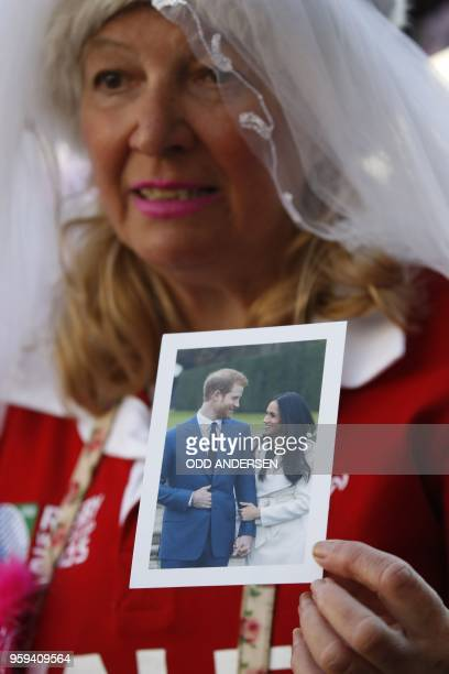 Royal wellwisher Anne Daly holds a photograph of Prince Harry and his US fiancee Meghan Markle in Windsor on May 17 2018 two days before the royal...