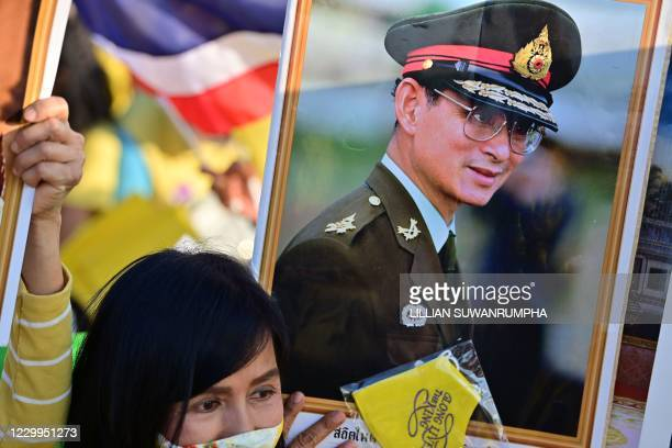 Royalist holds up a portrait of the late Thai king Bhumibol Adulyadej as they wait for the start of a ceremony to commemorate his birthday at Sanam...