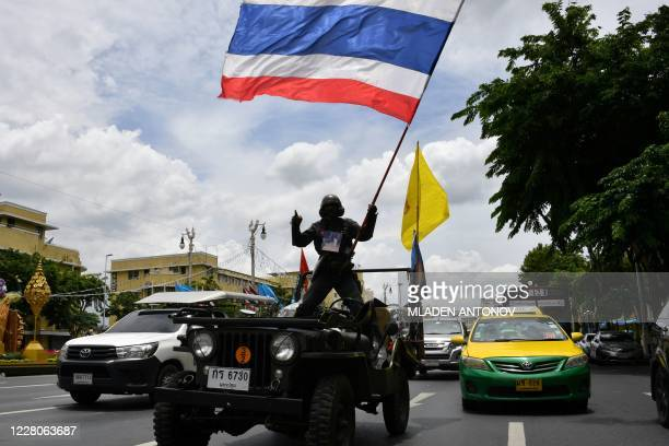 A royalist protester waves a Thai national flag as he stands on a vehicle driving past a rally in Bangkok on August 16 ahead of antigovernment...