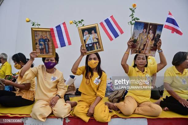 Royalist supporters hol dup images of Thailand's King Maha Vajiralongkorn and Queen Suthida as they wait to catch a glimpse of him as he heads to the...