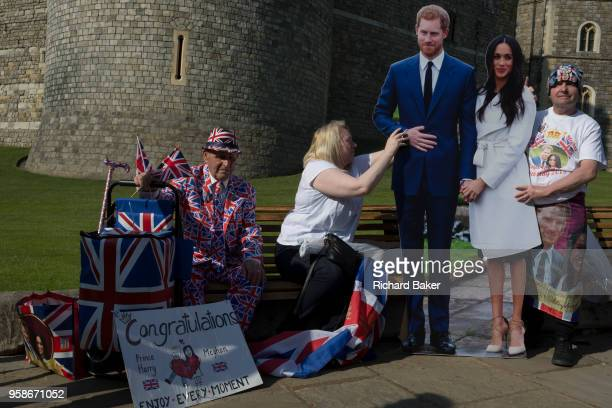 Royalists occupy benches outside Windsor Castle with a lifesize standee of Prince Harry and Meghan Markle as the royal town gets ready for the royal...