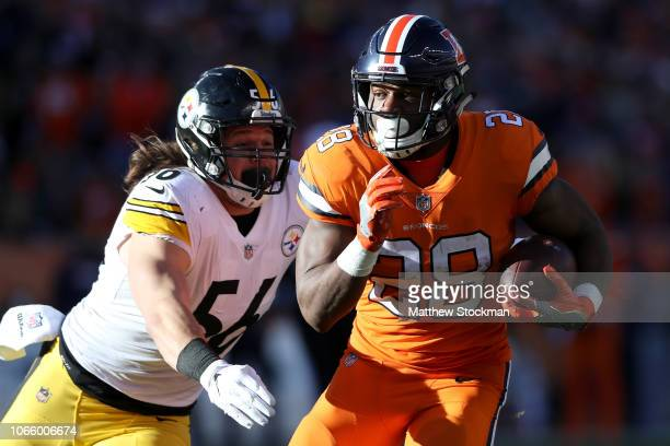 Royce Freeman of the Denver Broncos attempts to elude Anthony Chickillo of the Pittsburgh Steelers at Broncos Stadium at Mile High on November 25...