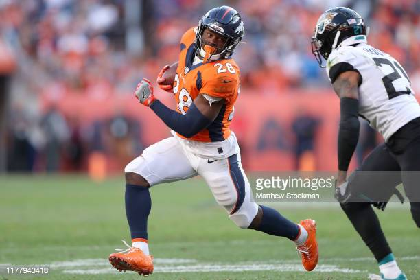 Royce Freeman of the Denver Broncos carries the ball against A.J. Bouye of the Jacksonville Jaguars in the fourth quarter at Empower Field at Mile...