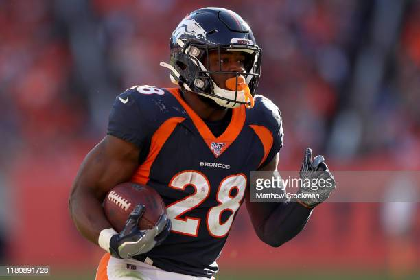 Royce Freeman of the Denver Broncos carries the ball against the Tennessee Titans in the third quarter at Broncos Stadium at Mile High on October 13,...
