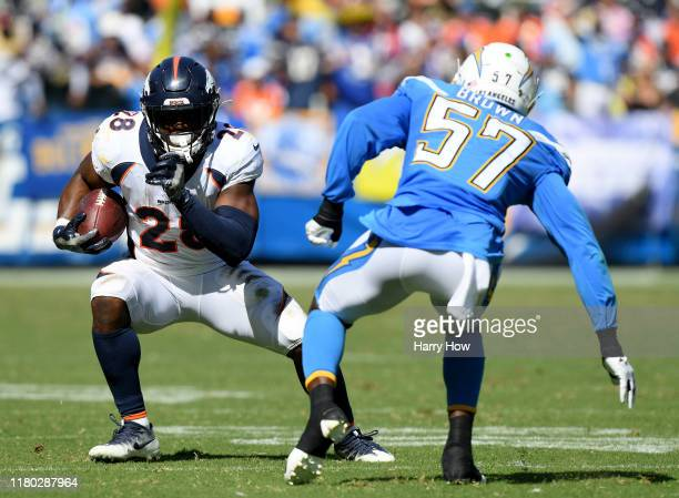Royce Freeman of the Denver Broncos cuts back on Jatavis Brown of the Los Angeles Chargers during the second quarter at Dignity Health Sports Park on...