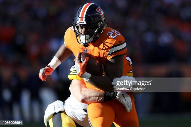 Royce Freeman of the Denver Broncos is tackled by Anthony Chickillo of the Pittsburgh Steelers at Broncos Stadium at Mile High on November 25 2018 in...