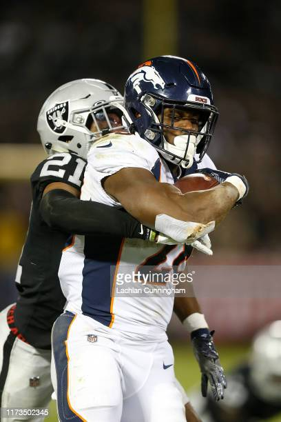 Royce Freeman of the Denver Broncos is tackled by Gareon Conley of the Oakland Raiders in the third quarter of the game at RingCentral Coliseum on...