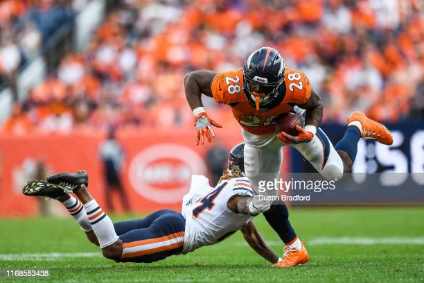 Royce Freeman of the Denver Broncos is tripped up by Buster Skrine of the Chicago Bears in the fourth quarter of a game at Empower Field at Mile High...
