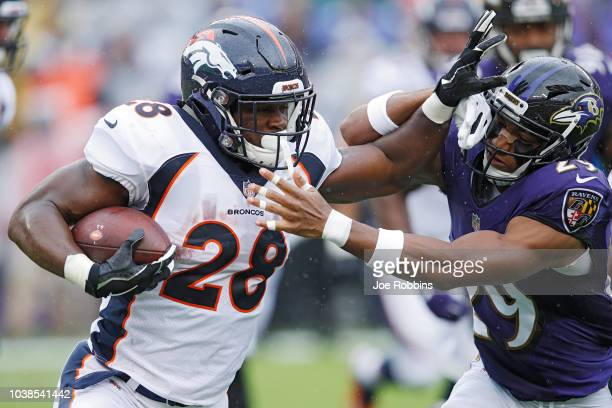 Royce Freeman of the Denver Broncos runs the ball while defended by Marlon Humphrey of the Baltimore Ravens in the first quarter of the game at M&T...