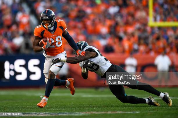 Royce Freeman of the Denver Broncos rushes against Quincy Williams of the Jacksonville Jaguars in the fourth quarter of a game at Empower Field at...
