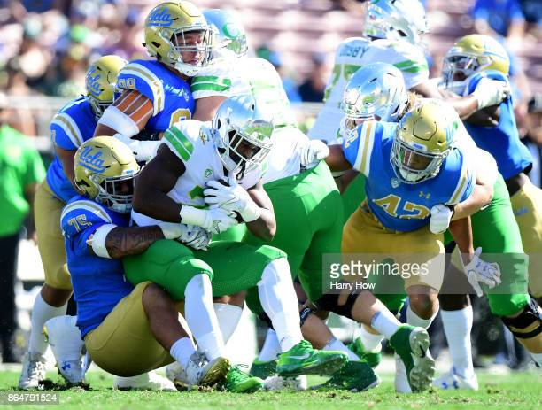 Royce Freeman of the Oregon Ducks is tackled by Boss Tagaloa of the UCLA Bruins during the first half at Rose Bowl on October 21 2017 in Pasadena...