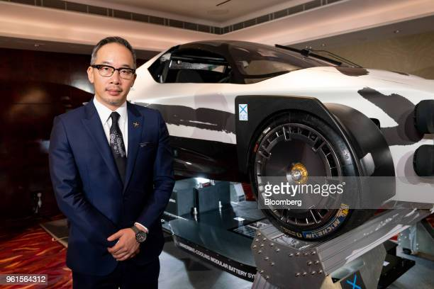 Royce Hong chief executive officer of Xing Mobility Inc poses for a photograph with the company's Miss R electric supercar following a Bloomberg...