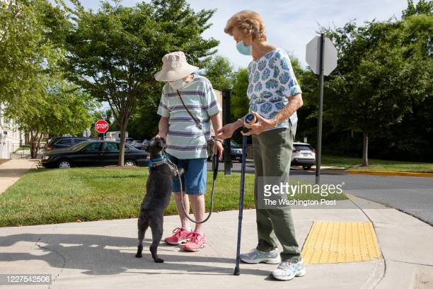 Roz Katz left gives her dog Meiko a treat while walking with her friend Mary Byrd outside of Ingleside at King Farm an assisted living facility in...