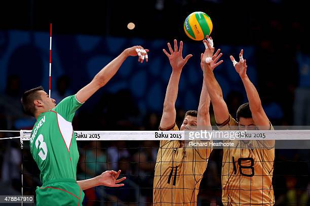 Rozalin Penchev of Bulgaria is blocked by Lukas Kampa and Michael Andrei of Germany during the Men's gold medal match between Bulgaria and Germany on...