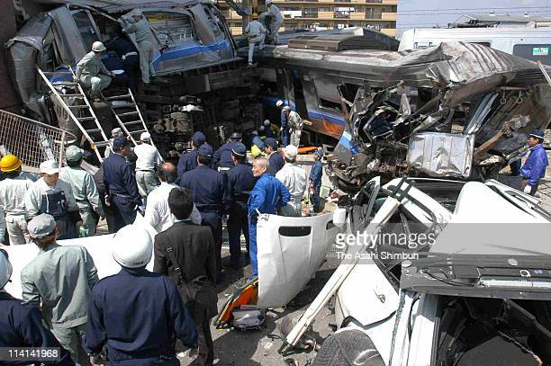 Rrescue workers attempt to free trapped passengers from a crushed commuter train after it derailed and plunged into an apartment building on April 25...