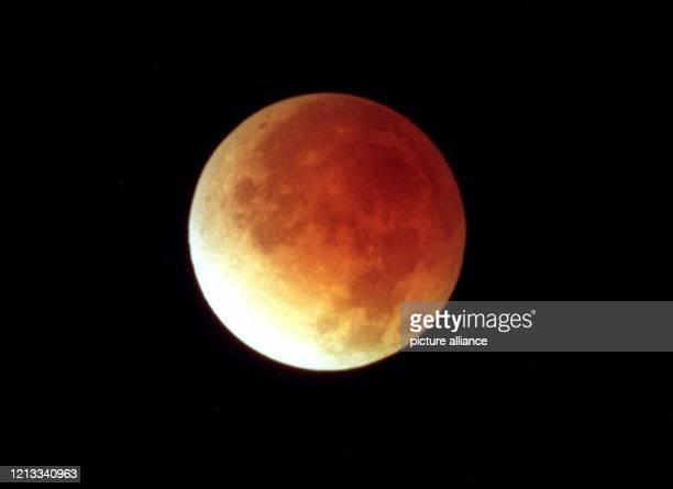Rötlich schimmert der Mond am frühen Morgen des 4.4.96 am Nachthimmel über Essen, nachdem ihn der Erdschatten fast komplett abgedeckt hatte. Vor...