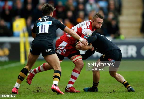 Ruan Ackermann of Gloucester tackled by Joe Simpson and Josh Bassett of Wasps during the Aviva Premiership match between Wasps and Gloucester Rugby...