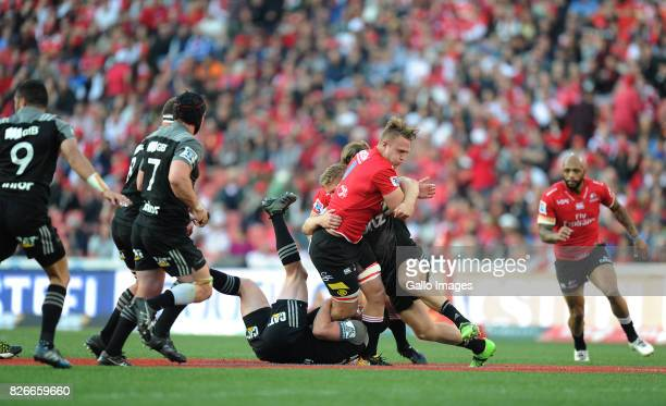 Ruan Ackermann of Lions is tackled by Jack Goodhue and Ryan Crotty of Crusaders during the Super Rugby Final match between Emirates Lions and...