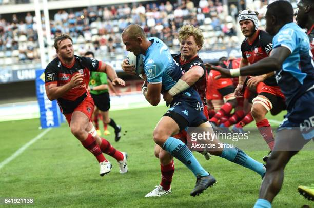 Ruan Piennar of Montpellier scores the second Try and James Hall of Oyonnax during the Top 14 match between Montpellier and Oyonnax on September 2...
