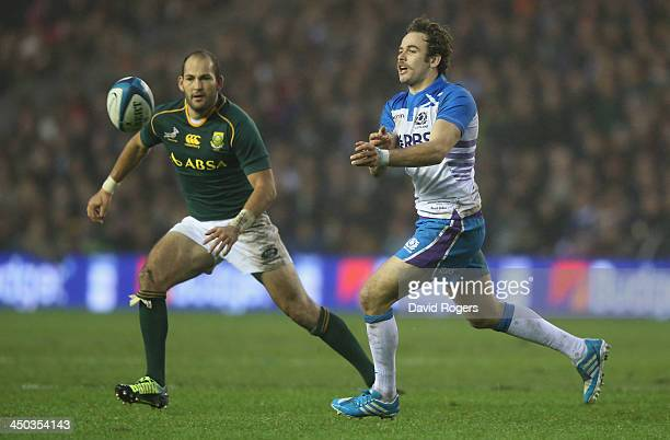 Ruaridh Jackson of Scotland passes the ball watched by Fourie du Preez during the International match between Scotland and South Africa at...