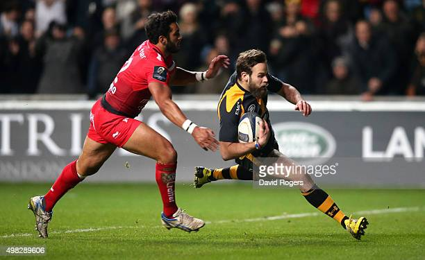 Ruaridh Jackson of Wasps breaks clear of Maxime Mermoz to score a try during the European Rugby Champions Cup match between Wasps and Toulon at the...
