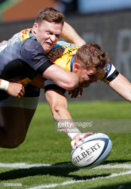 Ruaridh McConnochie of Bath Rugby scores his sides first try despite the efforts of Chris Ashton of Harlequins during the Gallagher Premiership Rugby...