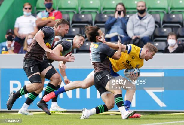 Ruaridh McConnochie of Bath Rugby scores his sides third try despite the efforts of Danny Care of Harlequins during the Gallagher Premiership Rugby...