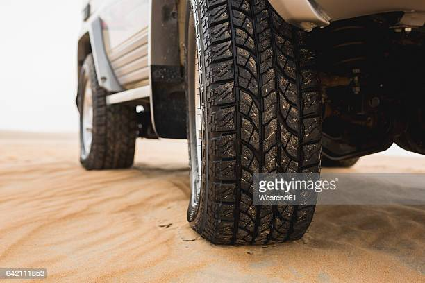 UAE, Rub al Khali, off-road vehicle parked in the desert, partial view