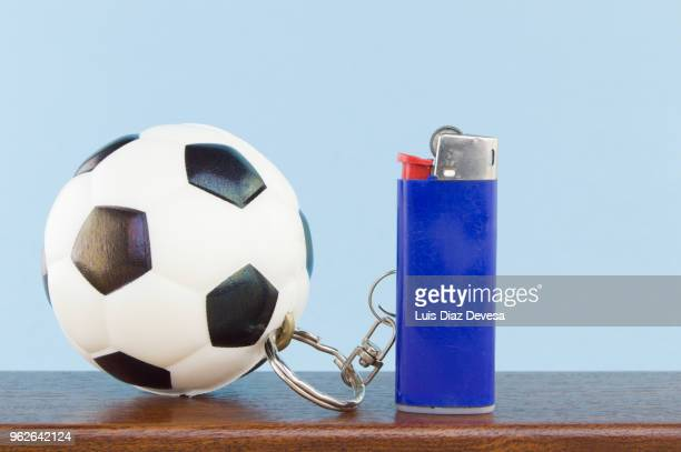 rubber ball football keyring holding blue cigarette lighter - football league imagens e fotografias de stock