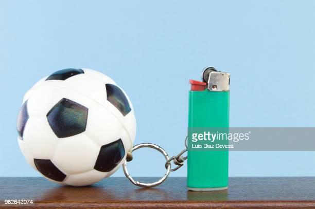 rubber ball football keyring holding green cigarette lighter - football league imagens e fotografias de stock