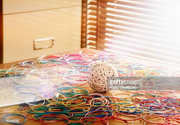 rubber band ball surrounded by colour rubber bands - newpremiumuk stock pictures, royalty-free photos & images