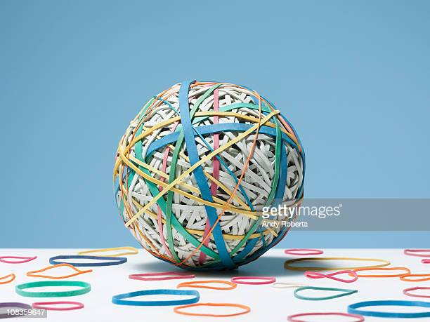rubber bands surrounding rubber band ball - gummi stock-fotos und bilder