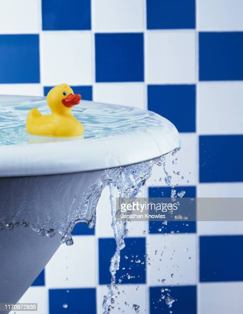 rubber duck in overflowing bath - rubber duck stock pictures, royalty-free photos & images