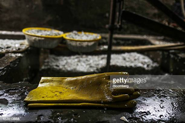 Rubber gloves sit beside pits containing shredded plastic waste for recycling in the Dharavi slum area of Mumbai India on Monday Aug 11 2014 Almost a...