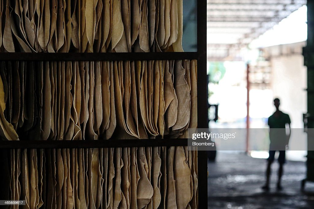 Rubber sheets hang from a rack to dry at the Thai Hua Rubber Pcl factory in Samnuktong, Rayong province, Thailand, on Wednesday, Jan. 29, 2014. Rubber production in Thailand, the world's largest exporter, may decline as growers from the main producing regions join protests seeking to overthrow the government, according to Von Bundit Co. Photographer: Dario Pignatelli/Bloomberg via Getty Images