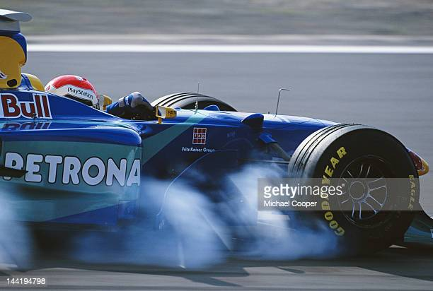 Rubber smoke pours off the front right tyre as Johnny Herbert of Great Britain driving the Red Bull Sauber Petronas Sauber C17 Petronas V10 locks up...