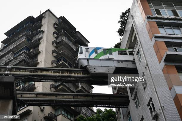 A rubberwheel lightrail train passes through a 19floor building which hosts Lizibai Station on May 9 2018 in Chongqing China The building was...