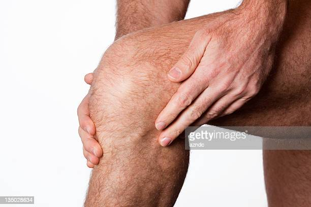 Rubbing sore knee with both hands