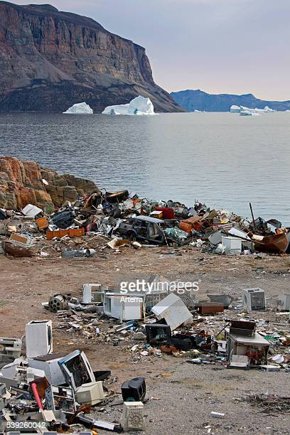 Rubbish at garbage dump and icebergs at the fishing village Uummannaq Greenland