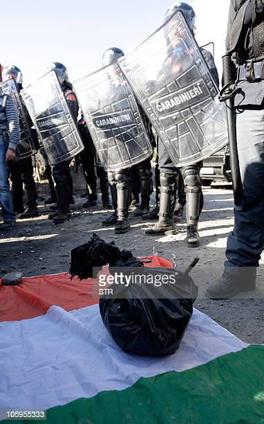 A rubbish bag rests on an Italian flag lies near police in Boscoreale near Naples on October 22 2010 during a protest against plans to build Europe's...