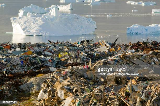 Rubbish dumped on the tundra outside Illulissat in Greenland with icebergs behind from the Sermeq Kujullaq or Illulissat Ice fjord The Illulissat ice...