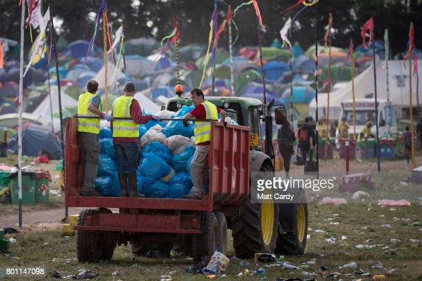 Rubbish is collected in front of the Pyramid Stage as festival goers leave the Glastonbury Festival site at Worthy Farm in Pilton on June 26 2017...