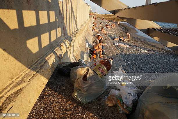 Rubbish is left under the steps as tourists relax on the municipal beach in Central Sochi Russia July 2015 The Russian Black Sea resort of Sochi...