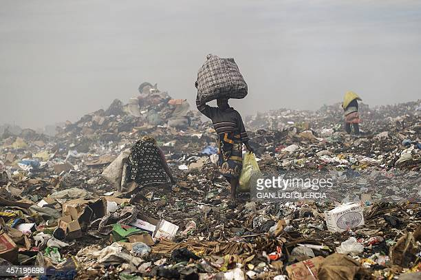 Rubbish pickers sift through garbage at the Maputo municipal garbage dumping site in Maputo on October 14 2014 Mozambique's upstart opposition vowed...